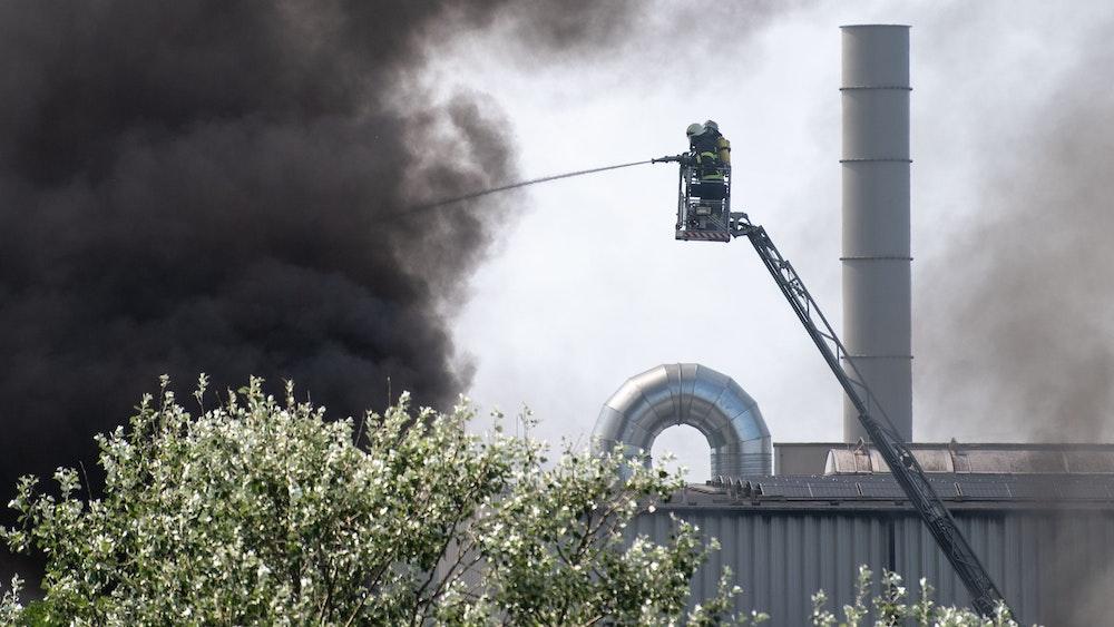 Erftstadt: Feuerwehrleute bekämpfen von einer Drehleiter aus einen Brand in einer Lagerhalle.
