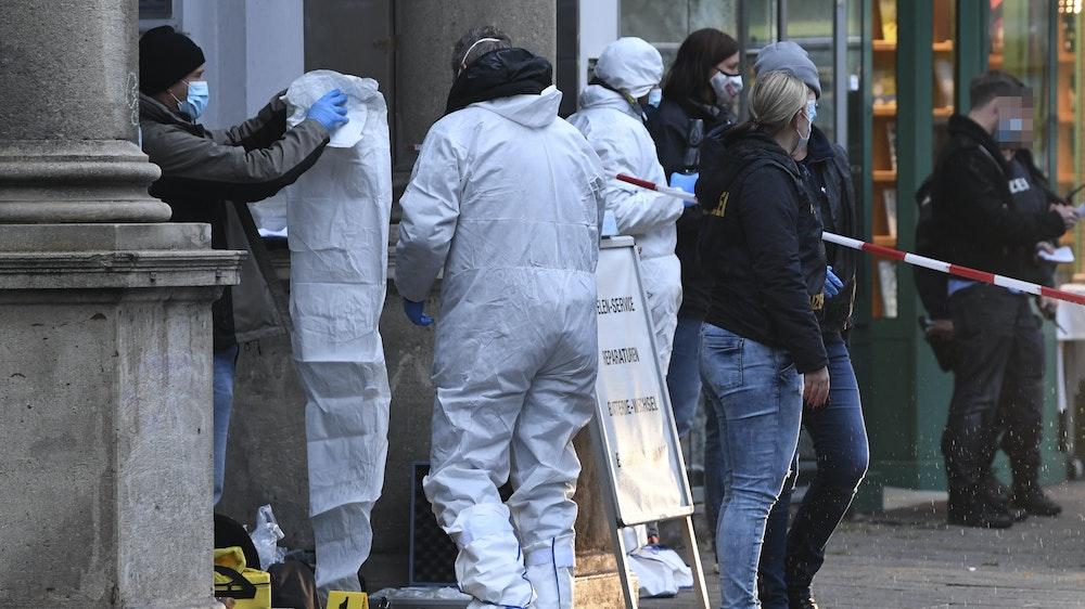 Polizisten und Beamte der Spurensicherung in Overalls ermitteln an einem Juweliergeschäft.