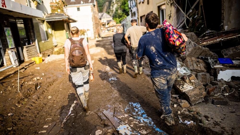 Mit Schlamm verschmierte Helfer und Helferinnen gehen durch Altenahr nach Hause.