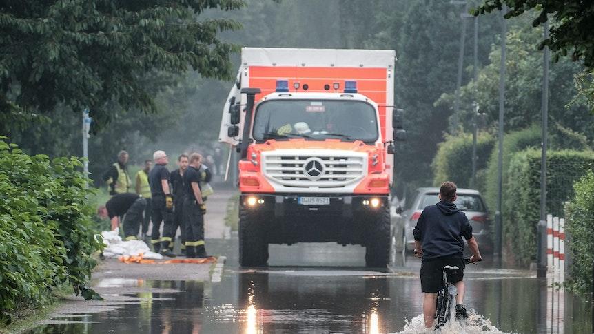 Ein Fahrradfahrer fährt am 14. Juli durch eine überflutete Straße in der Düsseldorfer Ostparksiedlung.