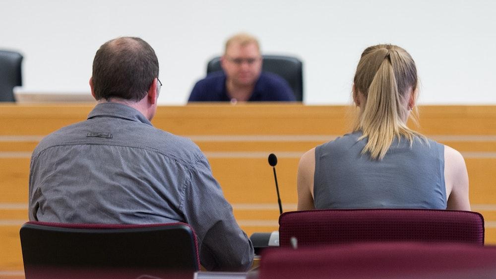 Ein Mann und eine Frau sitzen in einem Gerichtssaal vorm Richter.