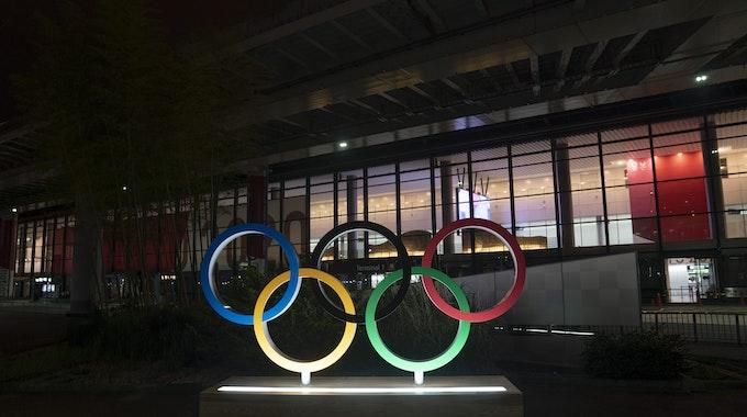 Die Olympischen Ringe werden im Dunkel vor dem Narita International Airport angeleuchtet.