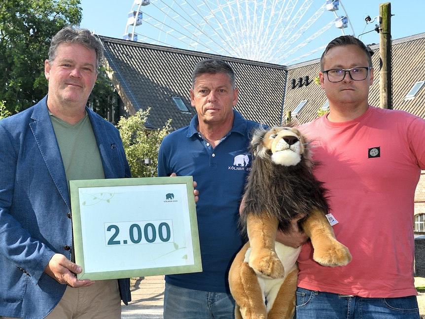 Drei Männer zeigen Plakat für 2000 Zoo-Tickets an Opfer der Flut-Katastrophe.