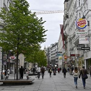 In einer Fußgängerzone in Wien spazieren einige Menschen umher.