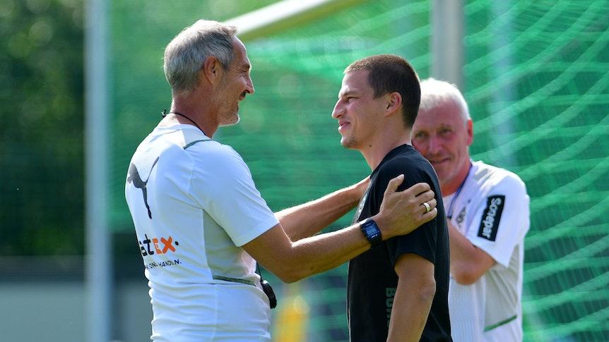 Adi Hütter hat seine Hände auf Lainers Schultern und beide lachen sich an.