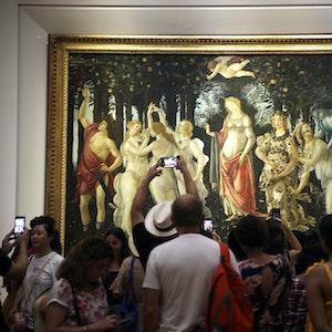 """Mehrere Museumsbesucher stehen vor einem großen Kunstwerk, dem """"Frühling"""" von Sandro Botticelli."""