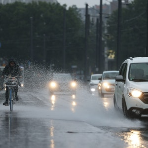 Eine Radfahrerin wird vom Spritzwasser eines Autos getroffen.