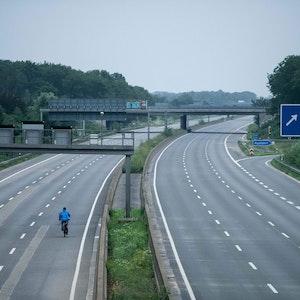 Ein Fahrradfahrer fährt über die gesperrte Autobahn A1 nahe Blessem in Erftstadt.