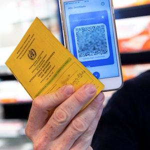Ein Apotheker hält einen Impfpass und einen digitalen Impfnachweis in den Händen. Die Ausstellung der digitalen Impfpässe wurde jetzt erstmal gestoppt.