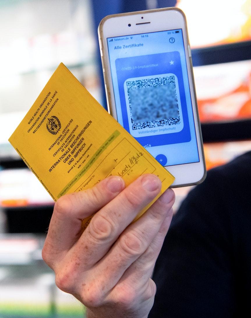 Ein Apotheker hält einen Impfpass und einen digitalen Impfnachweis in den Händen.
