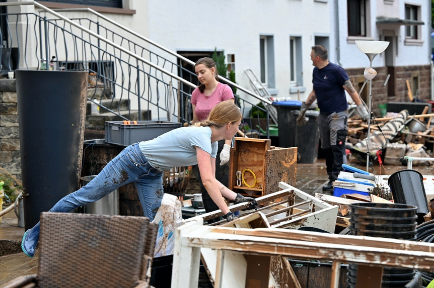 Die Menschen räumen nach dem Hochwasser zerstörte Möbel auf die Straße.