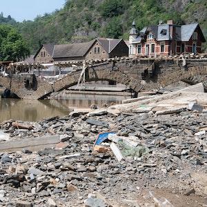 Eine zerstörte Eisenbahnbrücke über die Ahr. Im Vordergrund liegen Schutt und Trümmer.