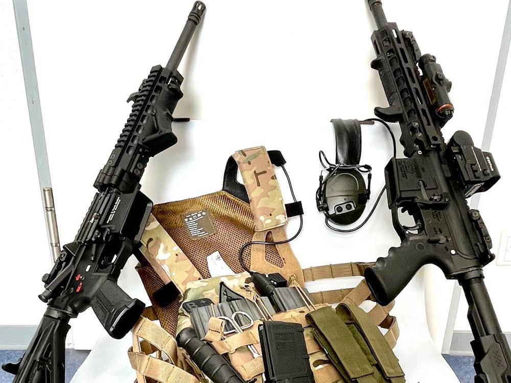 Mehrere Waffen, darunter zwei Sturmgewehre, liegen auf einem Haufen.