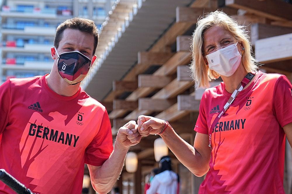 Wasserspringer Patrick Hausding (l) und Beachvolleyballspielerin Laura Ludwig begrüßen per Faustschlag vor der Pressekonferenz in Tokio.