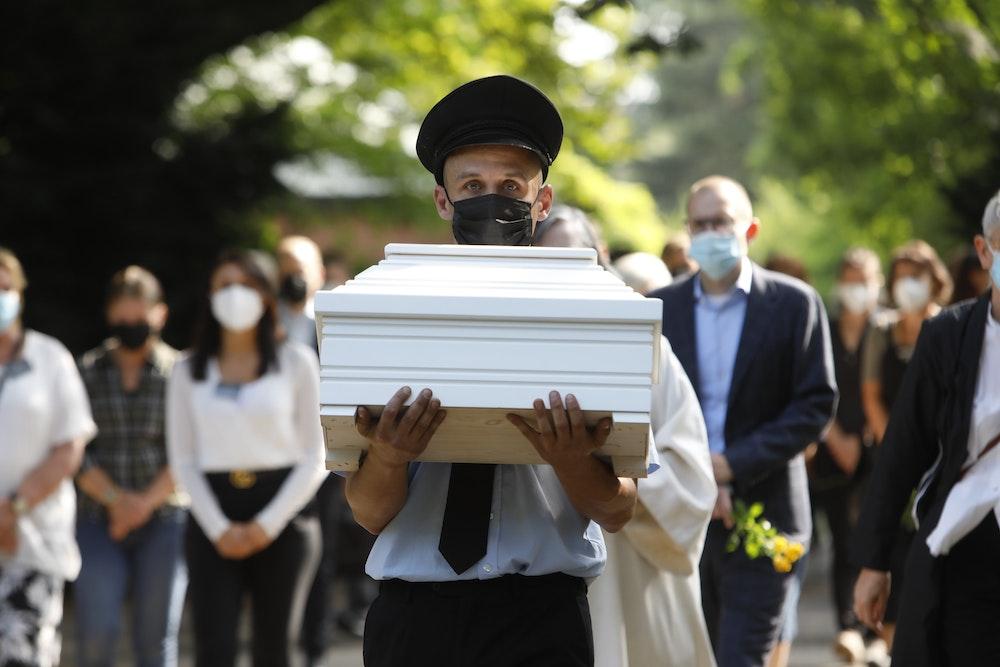 Ein Mann trägt einen kleinen, weißen Sarg. Zahlreiche Menschen folgen ihm.