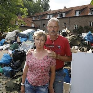 Iris und Rolf Friebel stehen in Hahn vor einem Müllberg aus Dingen, die beim Hochwasser zerstört wurden.