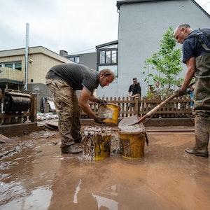Mit Eimern entsorgen Anwohner die Schlammmassen nach dem Hochwasser der Kyll.