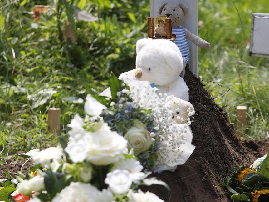 Zwei weiße Teddys, eine Plüschmaus sowie weiße Blumen liegen auf dem Grab.