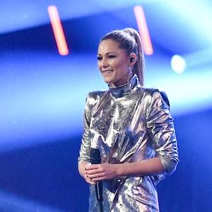 Helene Fischer steht mit Mikrofon Metallic-Outfit auf der Bühne