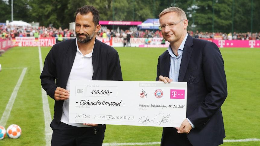 Eckhard Sauren und Bayerns Sportvorstand Hasan Salihamidzic übergeben einen Scheck.