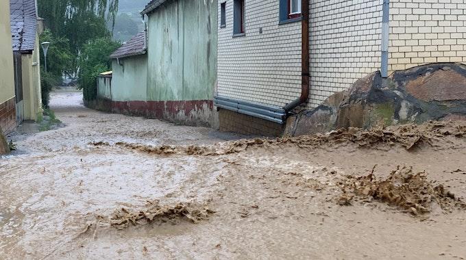 Wassermassen fluten eine Straße und fließen an Häusern vorbei.