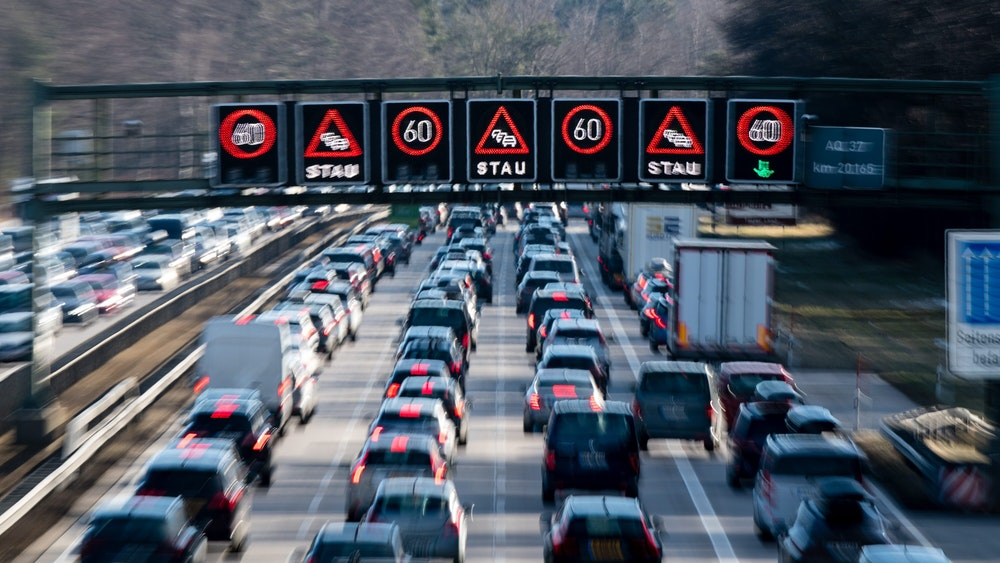 Dichter Verkehr schiebt sich über die Autobahn 8 in Fahrtrichtung Salzburg und Brenner-Autobahn im Hofoldinger Forst, während über der Straße auf einer digitalen Anzeige vor Stau gewarnt wird.