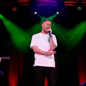 Rapper Mo-Torres steht in der Mitte auf der Bühne und singt.