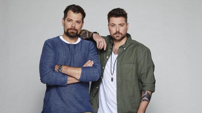 Daniel Fehlow steht mit verschränkten Armen links. Rechts neben ihm steht Felix von Jascherof, der seinen Arm auf Daniels Schulter legt.