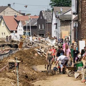 Helfer arbeiten auf einer von Matsch bedeckten Straße in Swisttal-Odendorf.