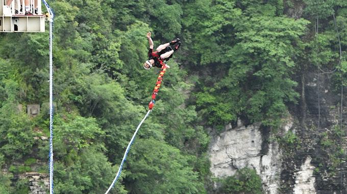 Ein Bungeespringer springt von der Glasbrücke Zhangjiajie in China.