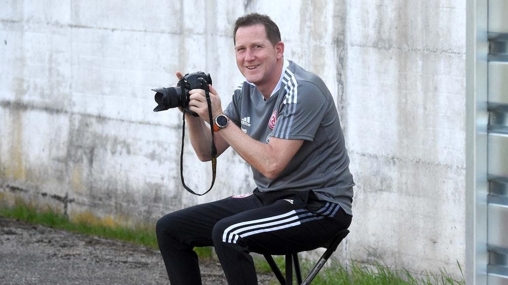 Uwe Klein posiert mit einem Fotoapparat in den Händen.