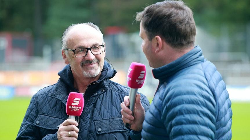 Jürgen Kohler hält bei einer TV-Schalte das Mikrofon von MagentaSport in der Hand.