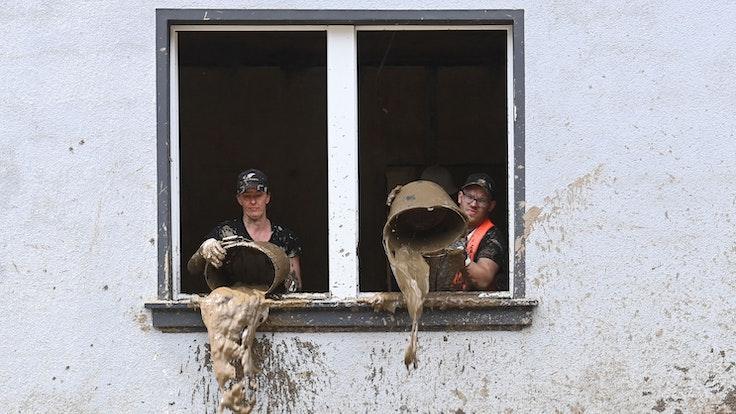 Unmittelbar nach der Flut kippen Helfer Schlamm aus Eimern in einem Haus in Dernau (Ahrtal)