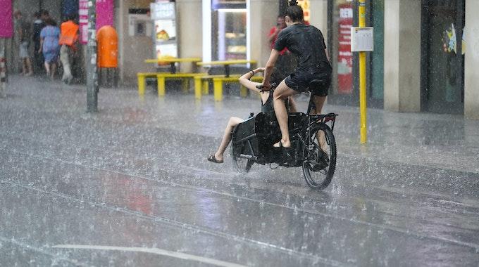 Junge Leute fahren mit einem Lastenfahrrad, während starker Regen auf die Friedrichstraße prasselt. +++ dpa-Bildfunk +++
