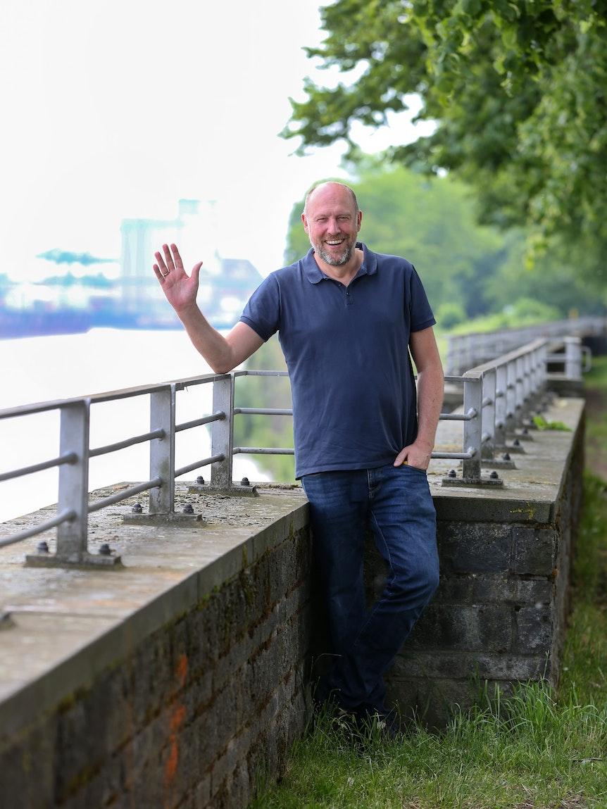 WDR-Moderator Sven Pistor winkt am Rhein in die Kamera