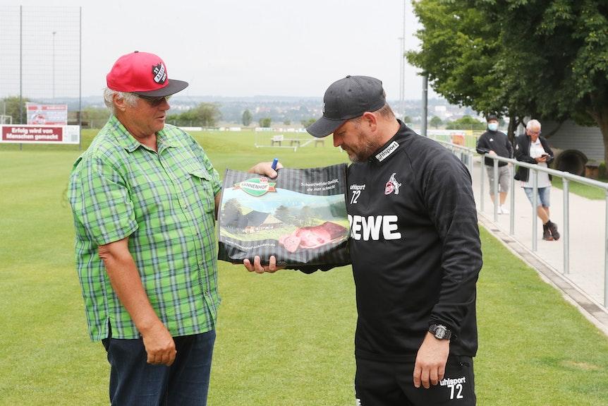 Steffen Baumgart wird im Trainingslager des 1. FC Köln mit einem Schinken überrascht.