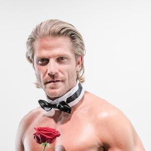 Ex-Bachelor Paul Janke mit nacktem Oberkörper, einer Fliege um den Hals und einer Rose in der Hand.