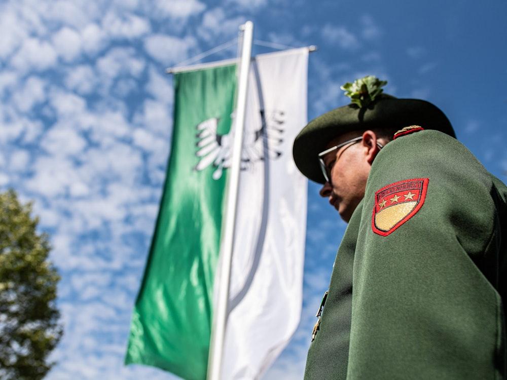 Warendorf: Ein Adjutant der Bürgerschützen Freckenhorst steht vor einer grün-weißen Schützenfahne.