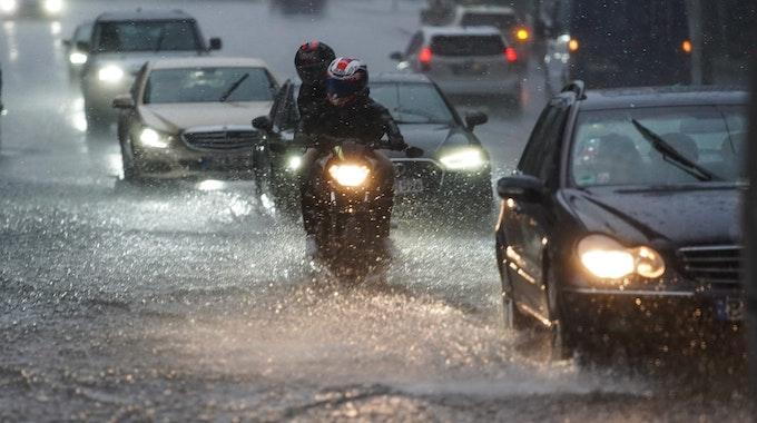 Autos und Motorräder fahren bei starkem Regen am 25.07.2021 über die überflutete Friedrichstraße in Berlin-Mitte.