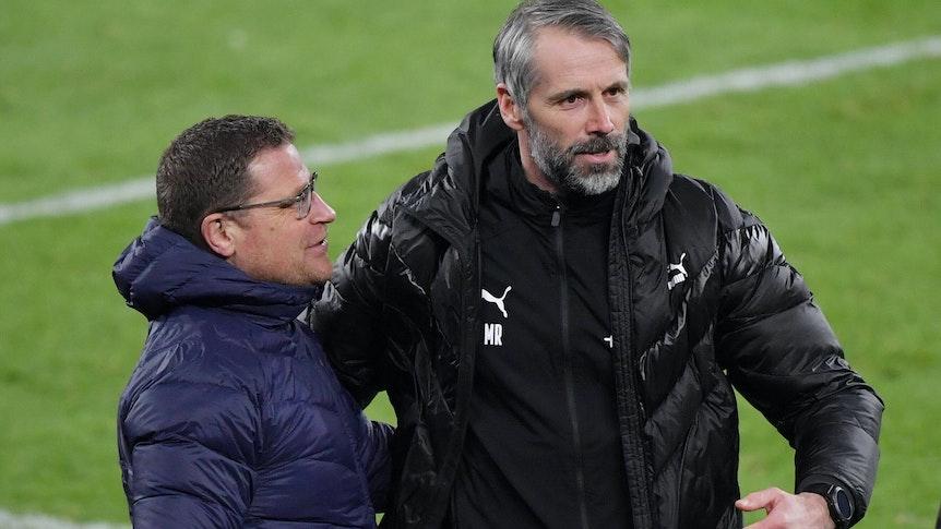 Trainer Marco Rose (rechts) und Gladbachs Manager Max Eberl (links) umarmen sich nach einem gewonnenen Bundesliga-Spiel.