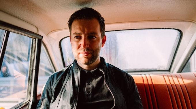 Sänger Josh. sitzt auf dem Rücksitz eines Autos und schaut durch das Fenster