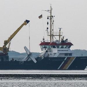 Das Wrack einer verunglückten Cessna hängt am Kran an Bord des Tonnenlegers im Wattenmeer vor Norderney. Beim Absturz des Kleinflugzeuges ist der 65 Jahre alte Pilot ums Leben gekommen.