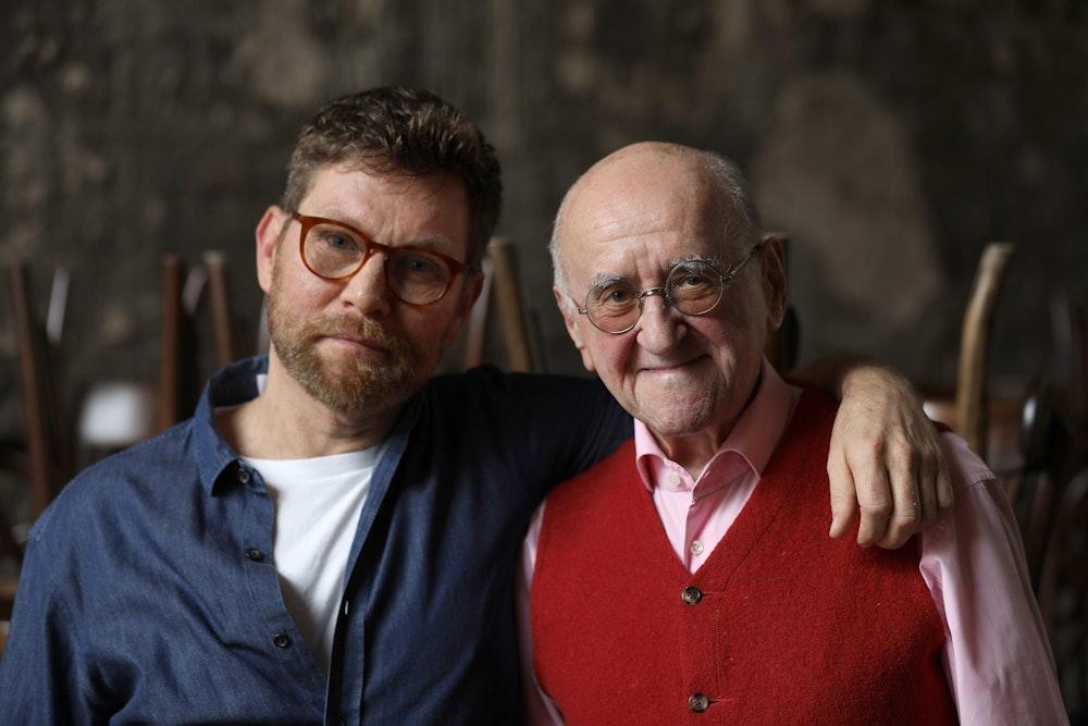 Alfred Biolek und sein Adoptivsohn Scott Biolek-Ritchie stehen zusammen in einem Restaurant in Köln.