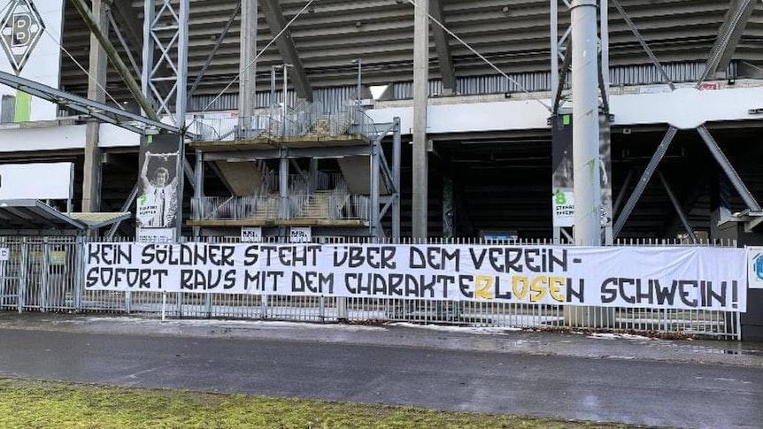 Ein riesiges Banner mit einer Hass-Parole gegen den ehemaligen Gladbach-Trainer Marco Rose hängt am 17. Februar 2021 am Stadionzaun in Mönchengladbach.