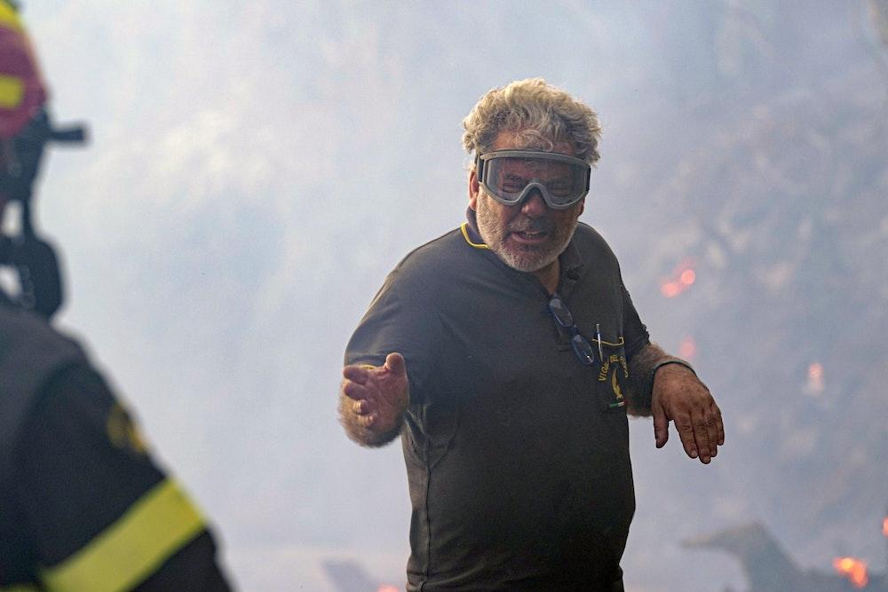 Ein Feuerwehrmann spricht bei Löscharbeiten in der Nähe von Oristano mit seinem Kollegen.