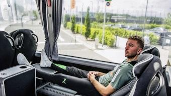 Christoph Kramer sitzt im neuen Mannschaftsbus von Borussia Mönchengladbach. Er hat die Beine hochgelegt und die Hände gefaltet.