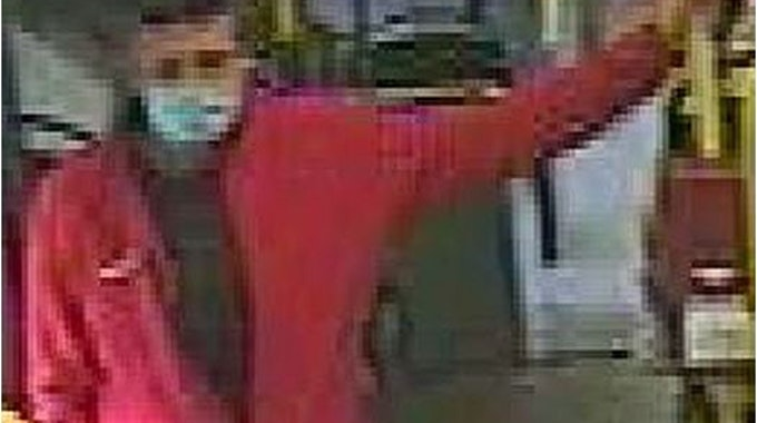 Mann in roter Jacke lehnt an Geländer in einem Bus in Köln.