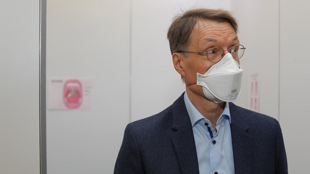 Karl Lauterbach steht mit Maske in studio dumont in Köln.
