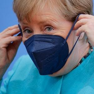 Angela Merkel zieht sich bei der Bundespressekonferenz am 22. Juli eine Maske auf.