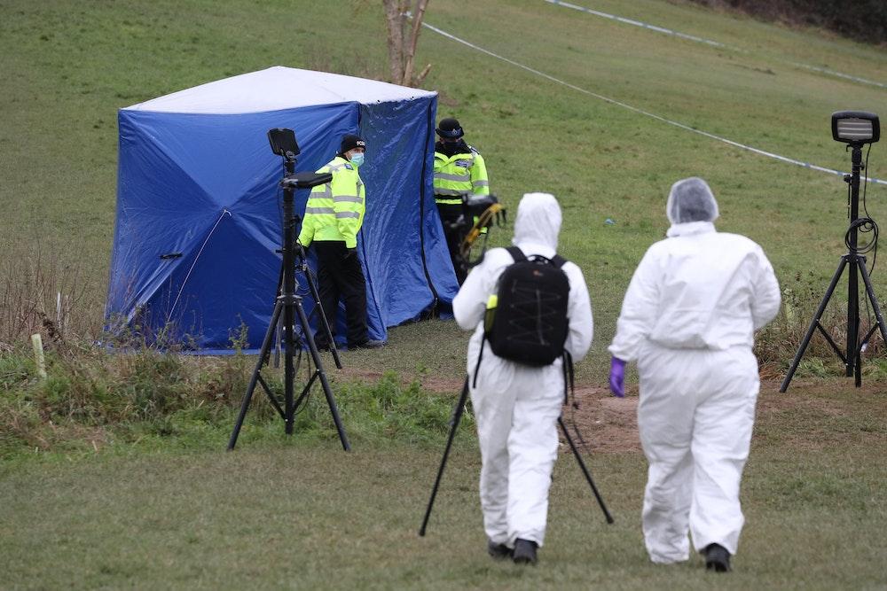 Zwei Gerichtsmediziner gehen in Richtung eines Zeltest am Tatort auf dem Bugs Bottom Feld.